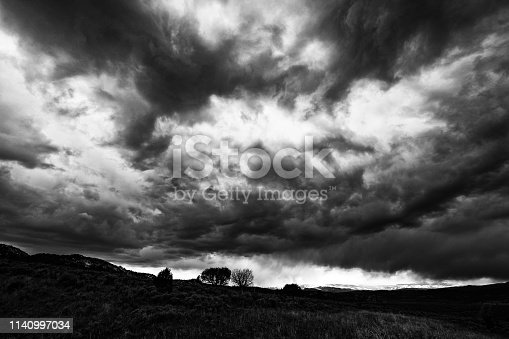 Dramatic Storm Clouds Landscape at Sunset - Clouds rolling in during storm right at sunset with mountain views. Black and white high-contrast dramatic photo.
