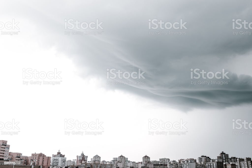 Dramatic stormy clouds over the modern city skyline. Rainy clouds...