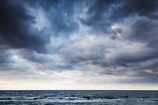 dramatic stormy dark cloudy sky over sea - dramatic sky stock photos and pictures