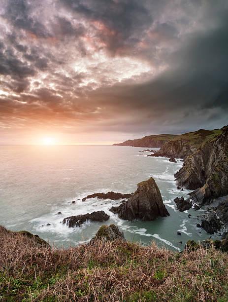 Dramatic stormy sunrise landscape over Bull Point in Devon Engla stock photo