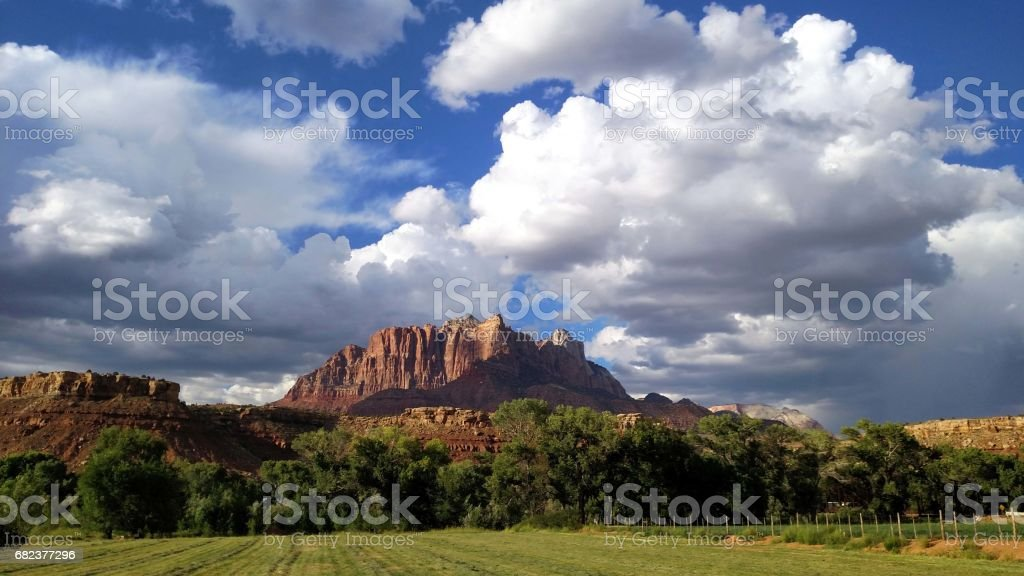 Dramatic summer clouds over Mt Kinesava and newly mowed pastures along the Virgin River in Rockville Utah looking into Zion National Park Utah royalty-free stock photo