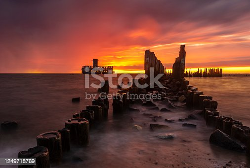Dramatic sunrise over the sea. Famous place on the Baltic coast, beach near the old torpedo plant from World War 2