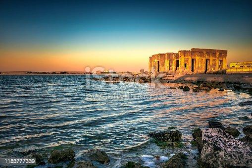 istock Dramatic sunrise with silky water view in Al uqair ruined fort sea side Saudi Arabia. 1183777339
