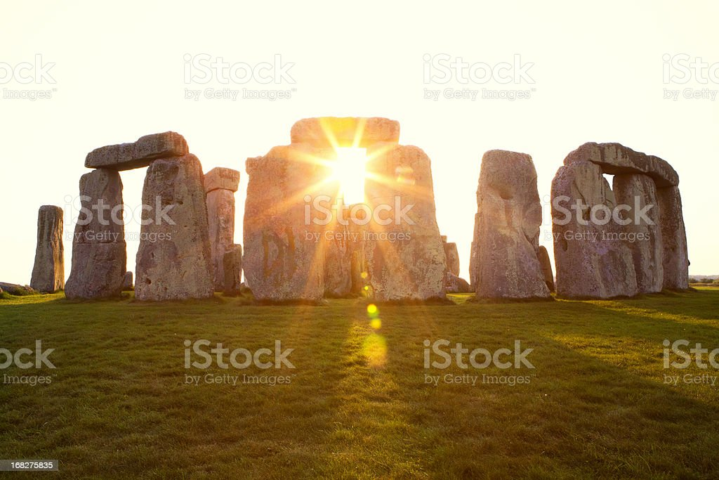 Dramatic Sunset at Stonehenge Horizontal Close-up view of ancient stones during sunset at UNESCO World Heritage Site at Stonehenge, Wiltshire, UK. Sun shines through the stones. Major tourist destination, archeological and pilgrimage site during Summer Solstice and Winter Solstice. Visible grain, softer focus. Ancient Stock Photo