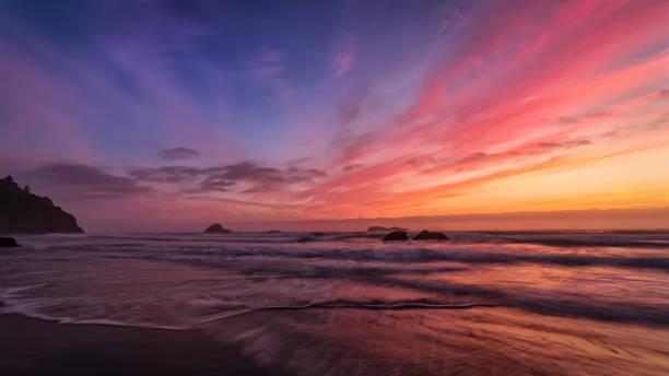 Dramatischer Sonnenuntergang am Strand, Farbbild – Foto