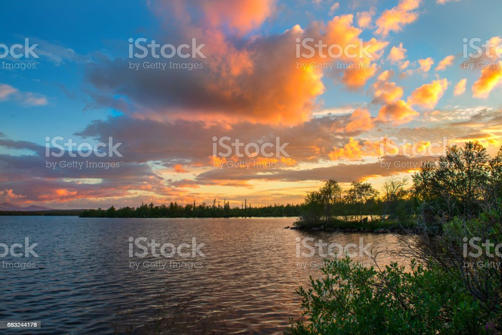 Dramatic sunset in the Arctic. The sun hiding behind the horizon, paints the clouds in a very beautiful color royalty-free 스톡 사진