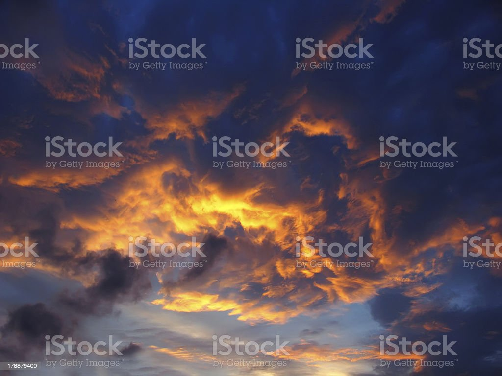 Dramatic sunset like fire in the sky with golden clouds royalty-free stock photo