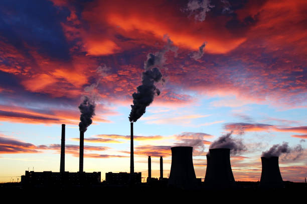 dramatic sunset on the sky and coal power plant factory - anidride carbonica foto e immagini stock