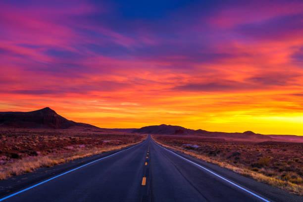 драматический закат над пустой дорогой в штате - sunset стоковые фото и изображения