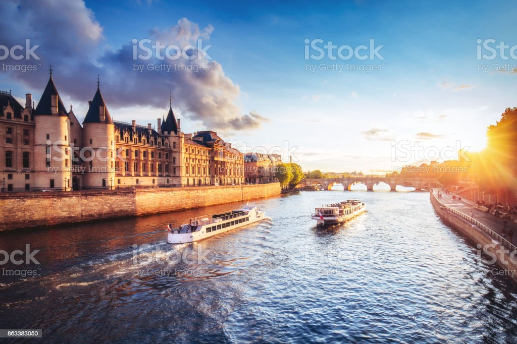 Dramatic sunset over river Seine in Paris, France, with Conciergerie and cruise boats. stock photo