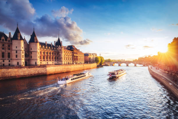 dramatic sunset over river seine in paris, france, with conciergerie and cruise boats. - river stock photos and pictures
