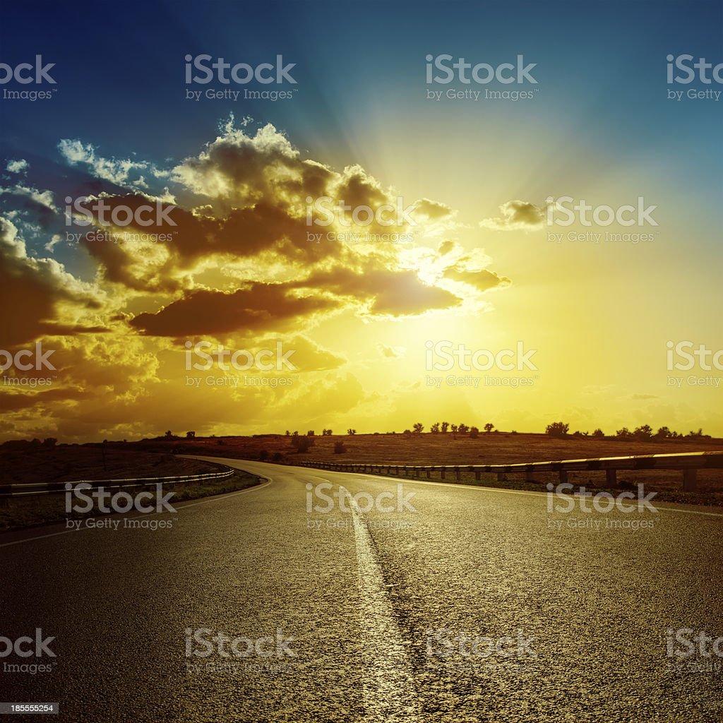 dramatic sunset over road to horizon royalty-free stock photo