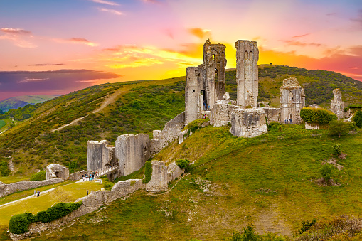 Corfe Castle is a fortification standing above the village of the same name on the Isle of Purbeck peninsula in the English county of Dorset. Built by William the Conqueror, the castle dates to the 11th century and commands a gap in the Purbeck Hills on the route between Wareham and Swanage.