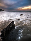 A dramatic sunset photo with corrugated weathered steel piles or pilings sticking out of the choppy water and waves of Lake Michigan in Chicago.