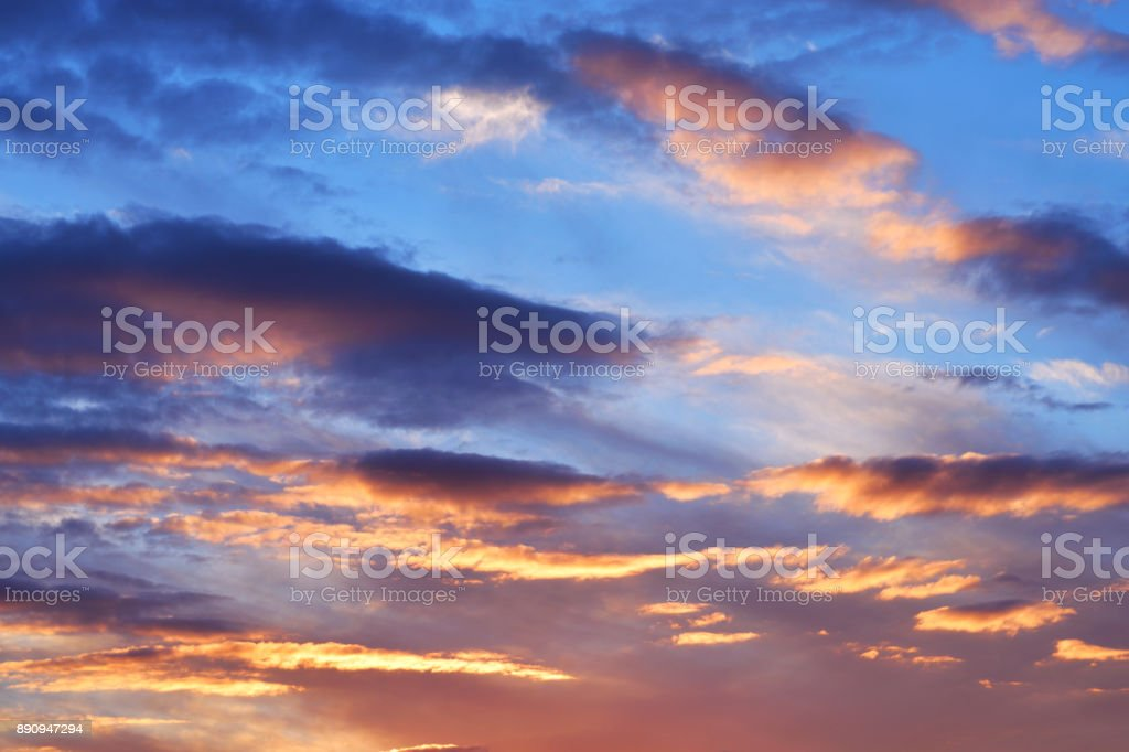 Dramatic sunset sky with dark clouds and bright orange light. stock photo