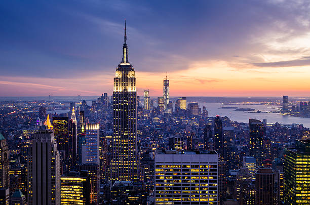 Dramatic sunset view highlighting the Empire State Building New York City with skyscrapers at sunset new york state stock pictures, royalty-free photos & images