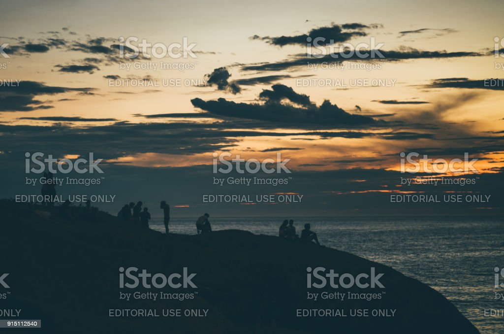 Dramatic sunset with group of people on seashore stock photo