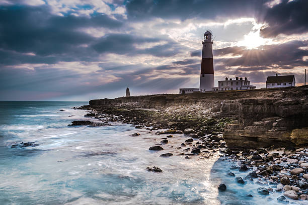 Dramatic sunset with iconic lighthouse on coast stock photo