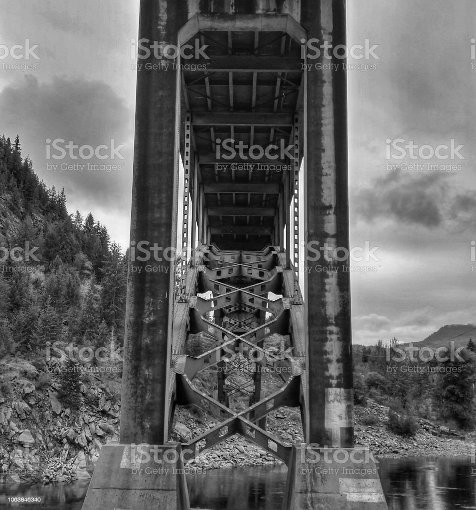 A dramatic view from under a large bridge crossing a river stock photo
