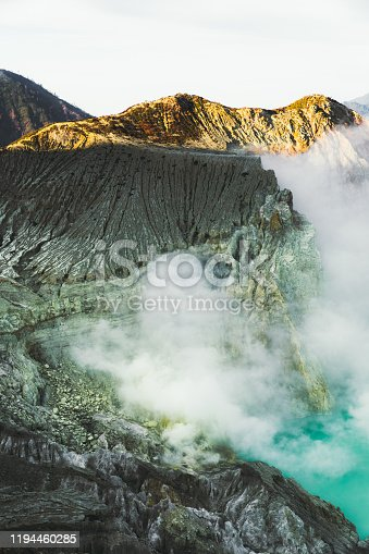 istock Dramatic view of turquoise colored lake in he crater of Ijen volcano, mountains and sulfur vapor on East Java, Indonesia 1194460285