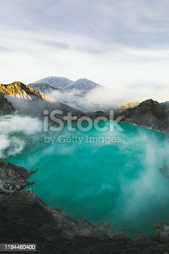 istock Dramatic view of turquoise colored lake in he crater of Ijen volcano, mountains and sulfur vapor on East Java, Indonesia 1194460400