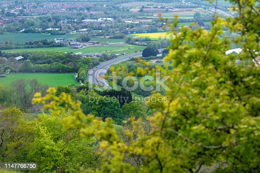 Dramatic view over the Cotswold Landscape showing the A417 dual carriageway heading towards Gloucester, patchwork fields of yellow oil seed, shot from Barrow Wake - A high vantage point near the village of Birdlip, high in the Cotswolds