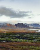 Scenic view of the beautiful mountain landscape, highway road and the seacoast in West Iceland