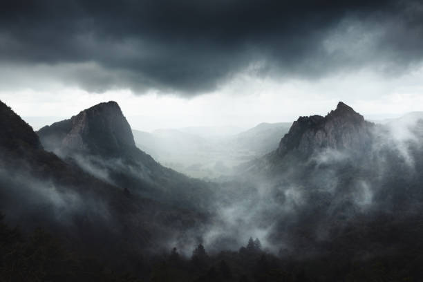Dramatic weather on Sanadoire and Tuilière rocks in Auvergne province - France Dramatic weather on Sanadoire and Tuilière rocks in Auvergne province - France valley stock pictures, royalty-free photos & images
