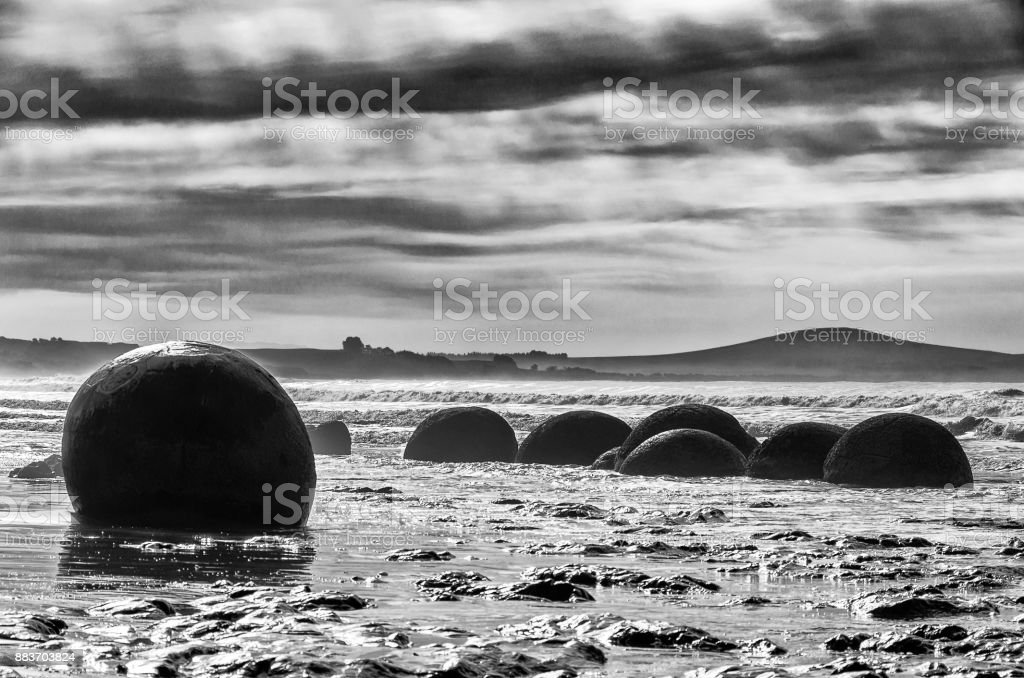 Dramatically Landscape with the Moeraki Boulders, New Zealand, rough grained ilford style. stock photo
