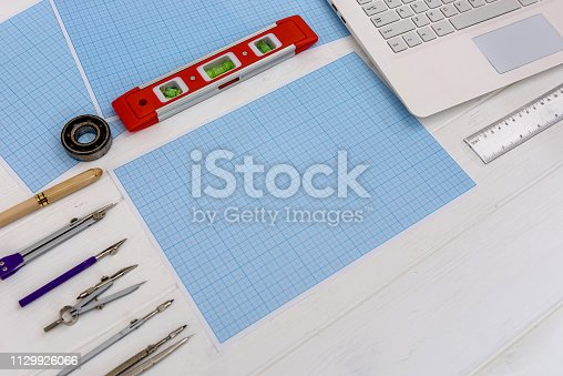 1060723604istockphoto Draughtsmanship equipment for drawing on millimeter paper with laptop 1129926066