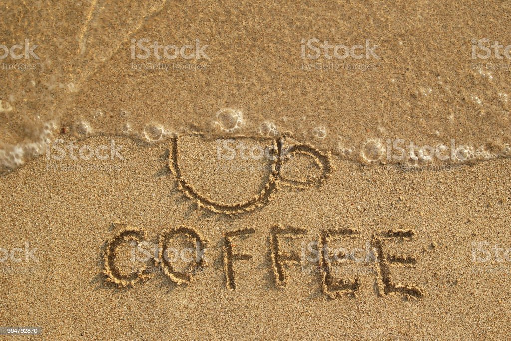 Drawing a cup washed away by a wave and inscription Coffee on the wet sand, top view. Healthy lifestyle concept. Stop drinking coffee. royalty-free stock photo