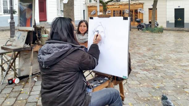 Drawing a portrait at Place du Tertre Paris stock photo