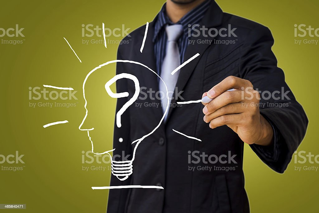 Drawing a question mark in the head lamp by businessman. stock photo