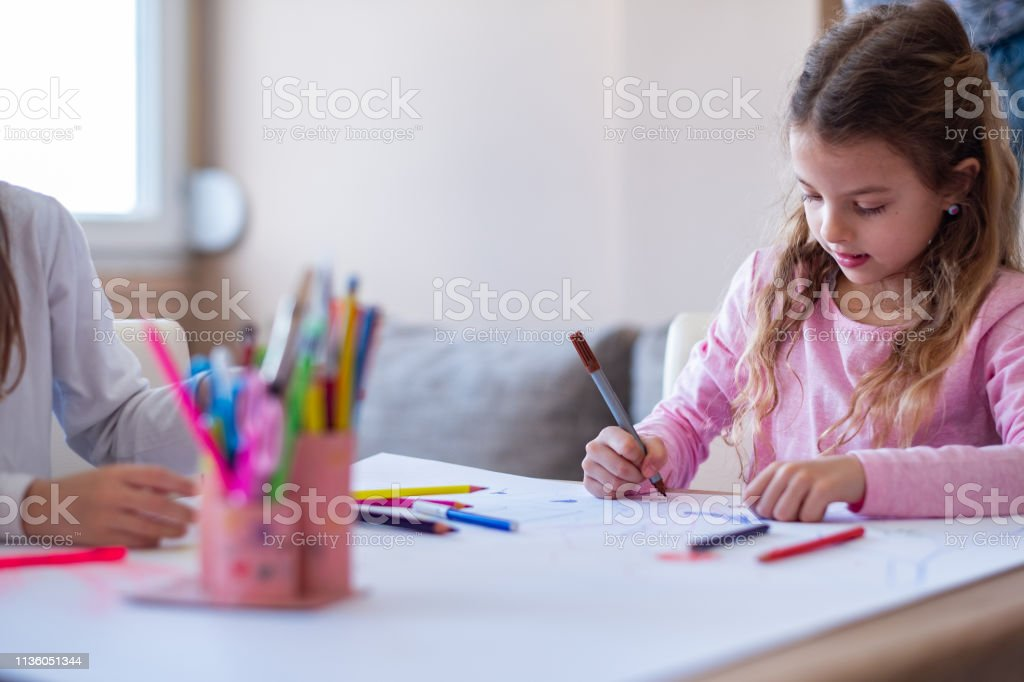 cute young girl is drawing on papir