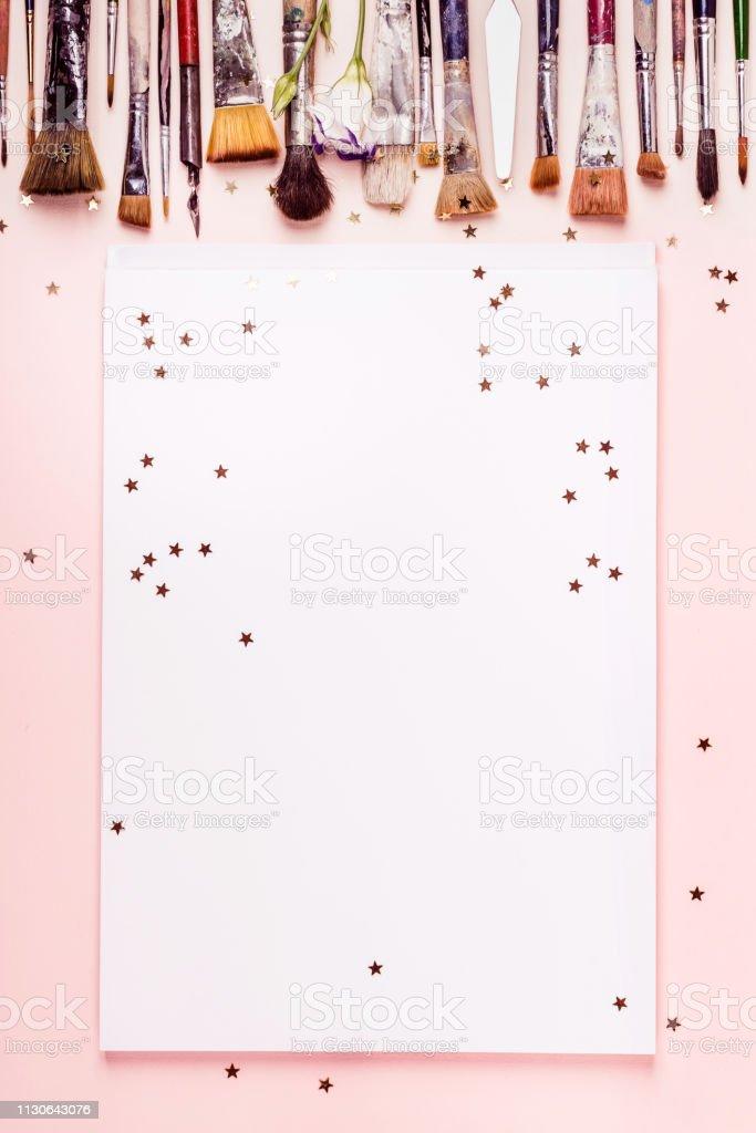 Marco de álbum de dibujo, pincel de fila y estrellas doradas sobre fondo rosa - foto de stock