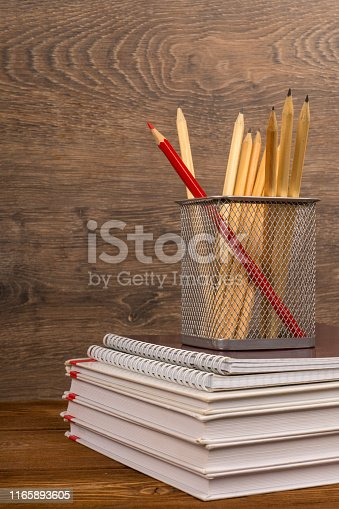 istock drawing and red pencils in basket on text and exercise books, education or back to school concept 1165893605
