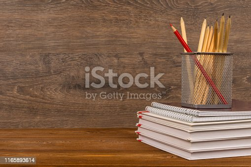istock drawing and red pencils in basket on text and exercise books, education or back to school concept 1165893614