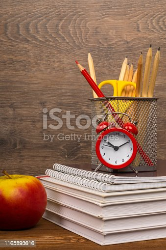 istock drawing and red pencils in basket on text and exercise books, education or back to school concept 1165893616