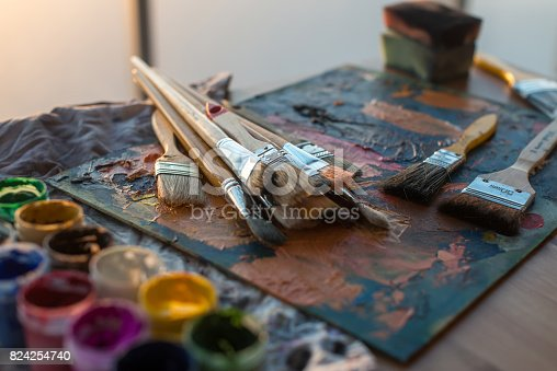 824254912 istock photo Drawing classes tools in art studio. Angle view photo of paintbrushes lying on palettewith oil paints brushstrokes mixture. 824254740