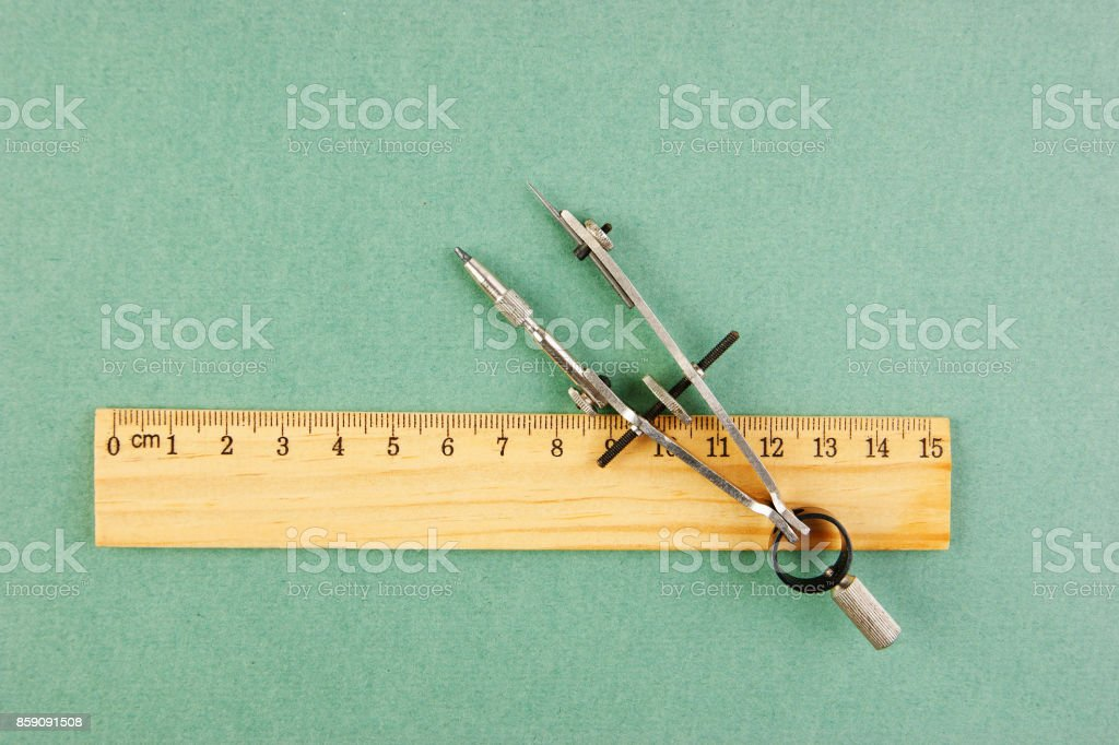 Drawing compass and wooden ruler on a green background stock photo