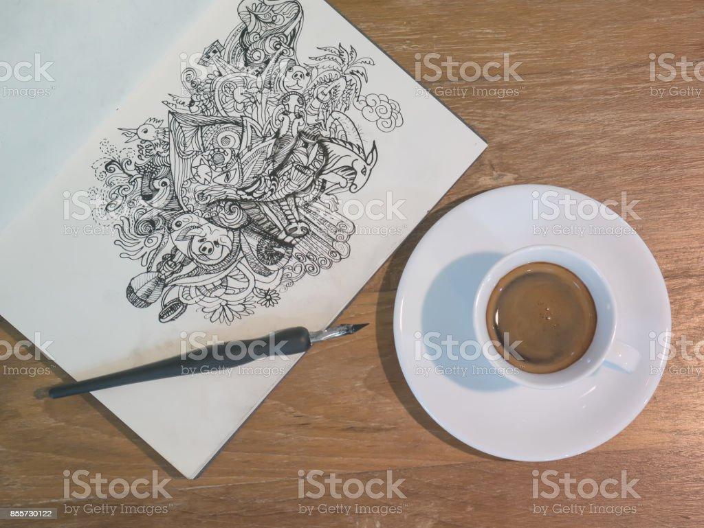 Zeichnung von Doodle Strichzeichnungen von schwarzer Tinte auf Papier mit einer Tasse Kaffee – Foto