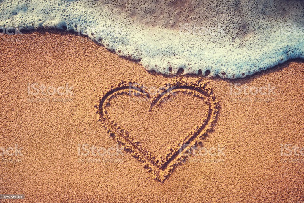 Drawing heart on the sand. Summer love background. stock photo