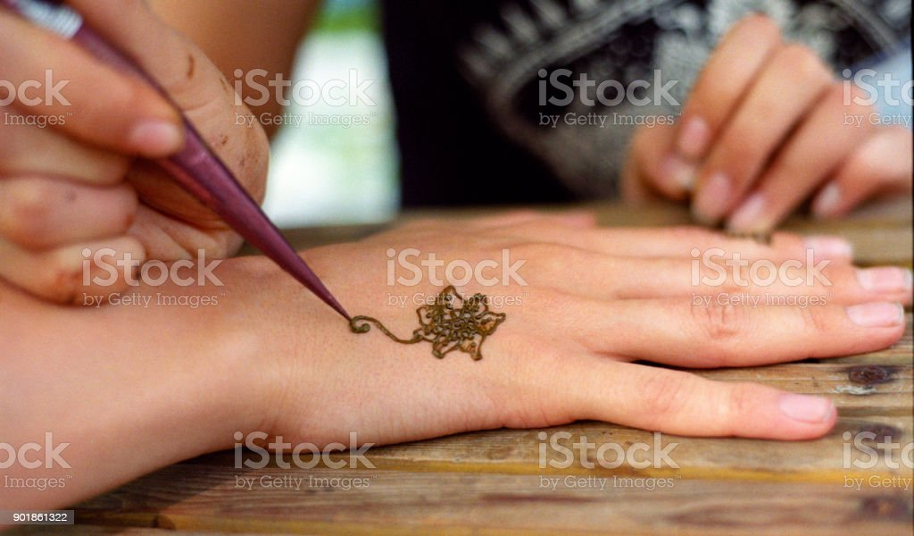 bbf06e6e2 Drawing henna tattoo, mehendi, on women hands. Shot on film - Stock image .