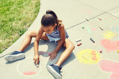 Shot of an adorable little girl drawing with chalk on the pavement outdoors