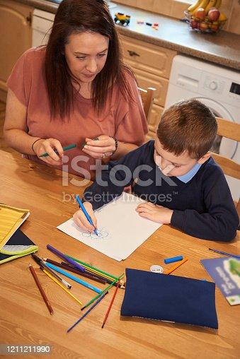 858130938 istock photo Drawing homework pictures with mummy 1211211990