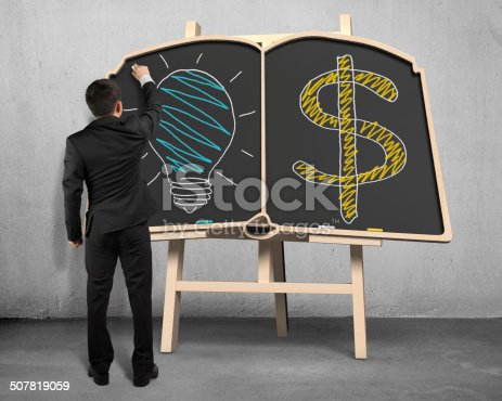 istock Drawing lamp and money symbol on blackboard 507819059