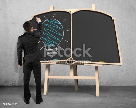 istock Drawing lamp on book shape blackboard 506573221
