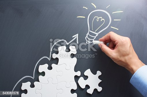 istock Drawing light bulb on blackboard. Steps shaped jigsaw puzzle. 543081578