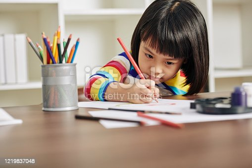 Adorable talented Asian girl sitting at desk at home and drawing with red pencil