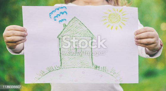 istock Drawing of a green house in the hands of a child. 1139335507